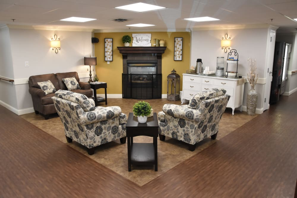 Community sitting area with floral couches and a fireplace at Corridor Crossing Place in Cedar Rapids, Iowa