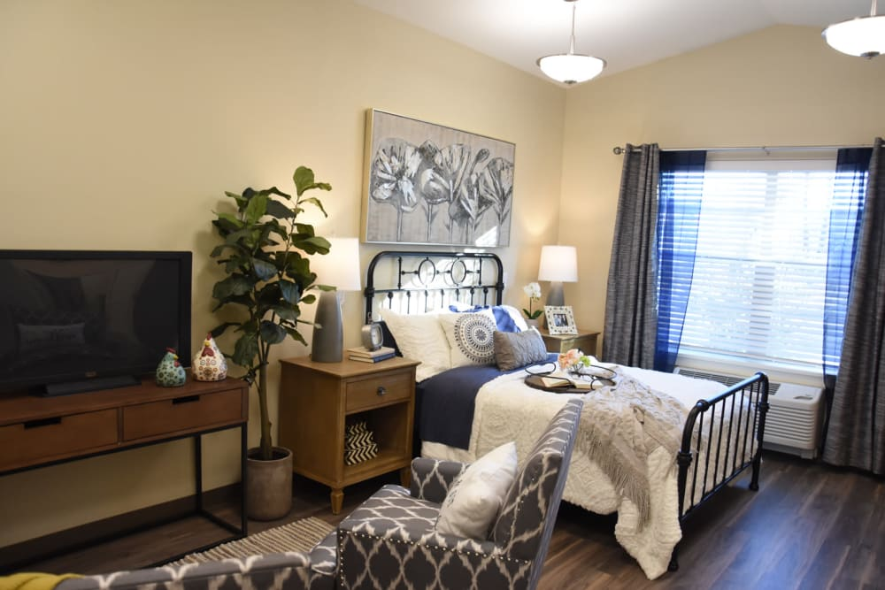 Well lit bedroom at Shadow Mountain Memory Care in Phoenix, Arizona featuring a large window, TV sitting area, and art on the walls