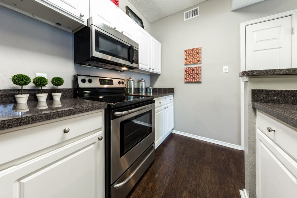 Kitchen with granite counters at Marquis at Legacy in Plano, Texas
