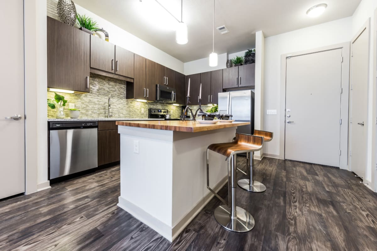 Modern style kitchen with island and counter stools at Marq Uptown in Austin, Texas