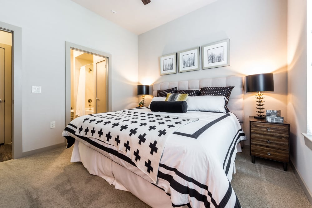 Queen size bed in carpeted bedroom with side tables and private bathroom at Marq Uptown in Austin, Texas