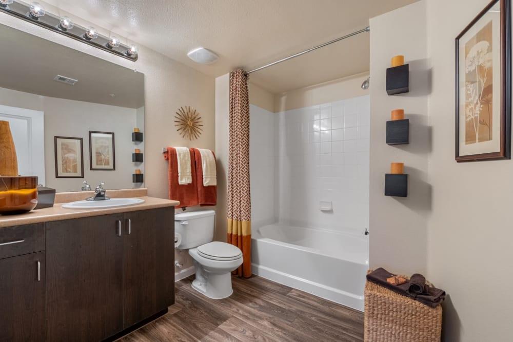 Desert tone style bathroom with wood flooring and bathtub at Marquis at Sonoran Preserve in Phoenix, Arizona