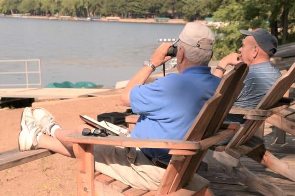 Two men take in the lakeside views, watching birds through binoculars, at Ebenezer Ridges Campus in Burnsville, Minnesota.