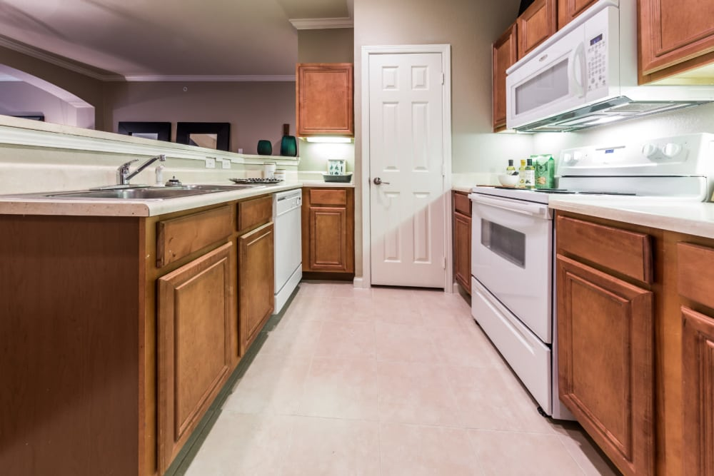 Bright kitchen with white appliances and wood cabinets and separate closed pantry at Marquis at The Cascades in Tyler, Texas