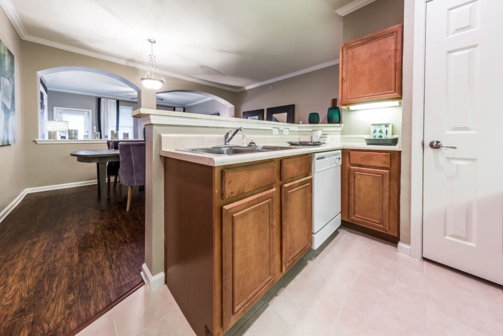 Bright kitchen with white appliances and wood cabinets facing dining area at Marquis at The Cascades in Tyler, Texas