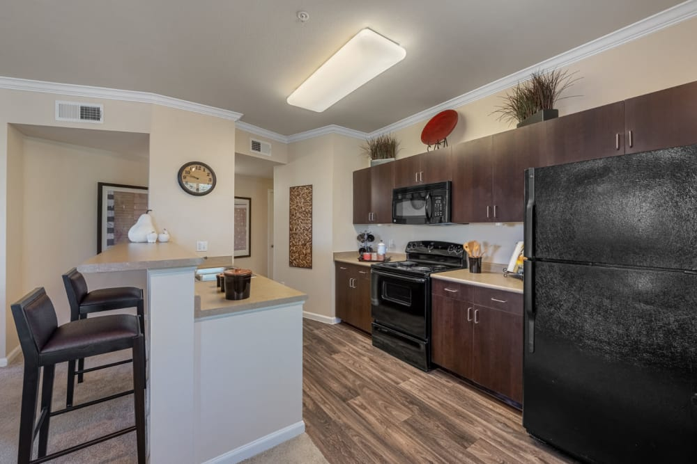 Bright and open kitchen with wood flooring and counter stool chairs at Marquis at Sonoran Preserve in Phoenix, Arizona