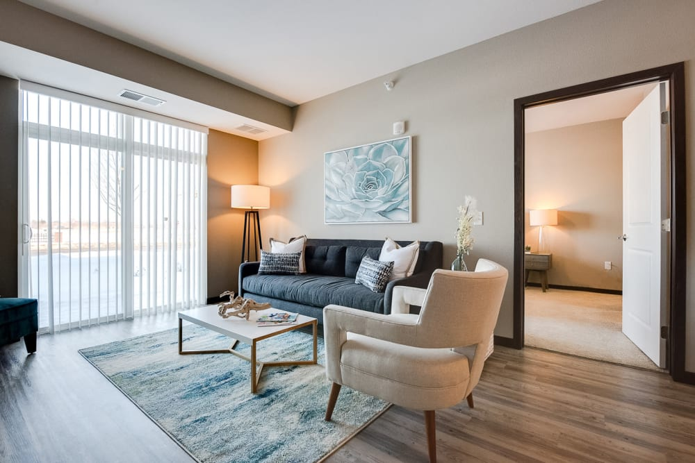 Beautiful, open living room with wood-style flooring at Remington Cove Apartments in Apple Valley, Minnesota