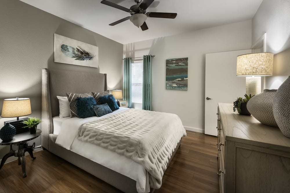 Large master bedroom with ceiling fan and beautiful furnishings in model home at The Maxx 159 in Goodyear, Arizona