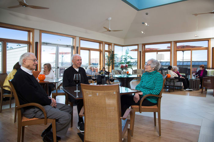 Residents enjoy dining in a naturally well lit room at All Seasons of Birmingham in Birmingham, Michigan