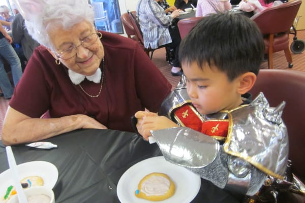 A resident decorating cookies with a child at Salmon Creek in Boise, Idaho