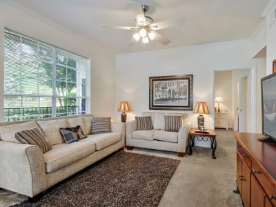 Living room with ceiling fans at Plantation Apartments in Gulfport, Mississippi