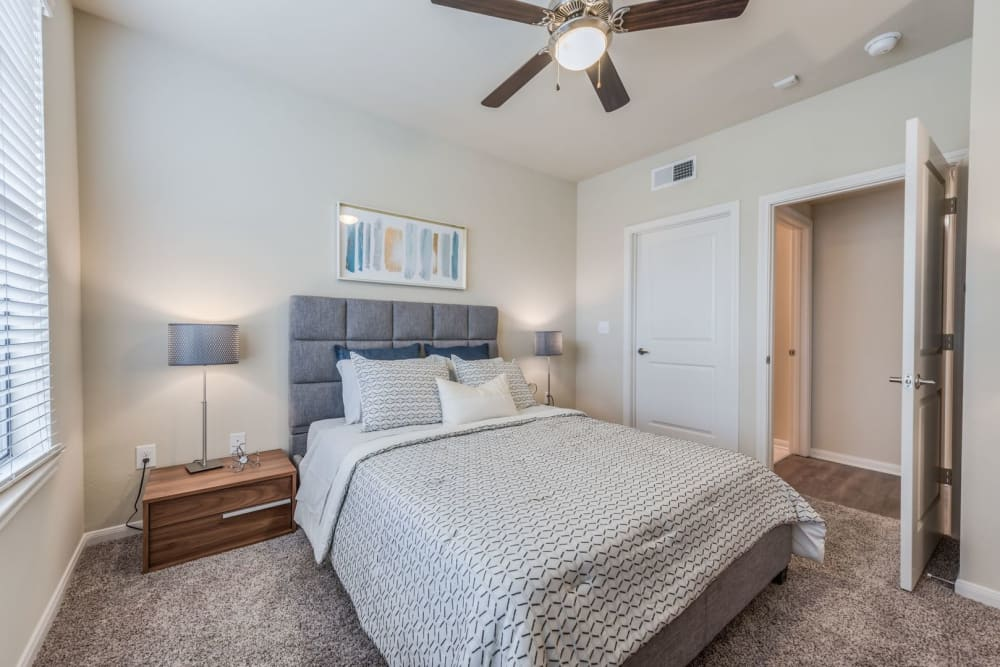 Model bedroom with plush carpeting and ceiling fan at Heights West 11th in Houston, Texas