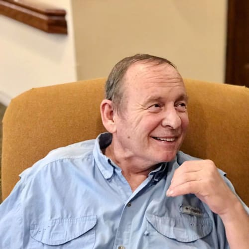 A seated resident smiling and looking off camera at Oxford Glen Memory Care at Carrollton in Carrollton, Texas