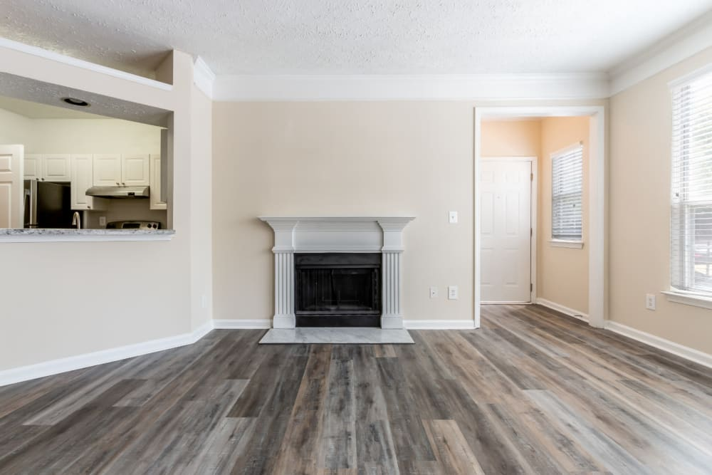 Open living area with fireplace and wood flooring at Marquis at Sugarloaf in Duluth, Georgia