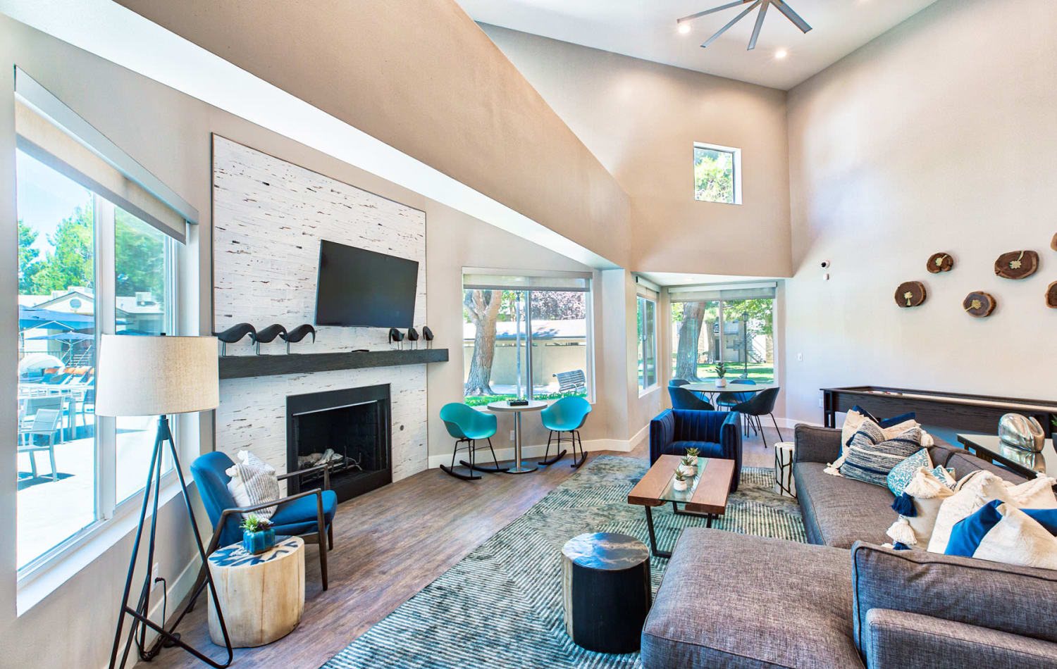 Luxurious clubhouse lounge area with huge bay windows, a flatscreen TV, and fireplace at Mountain Vista in Victorville, California