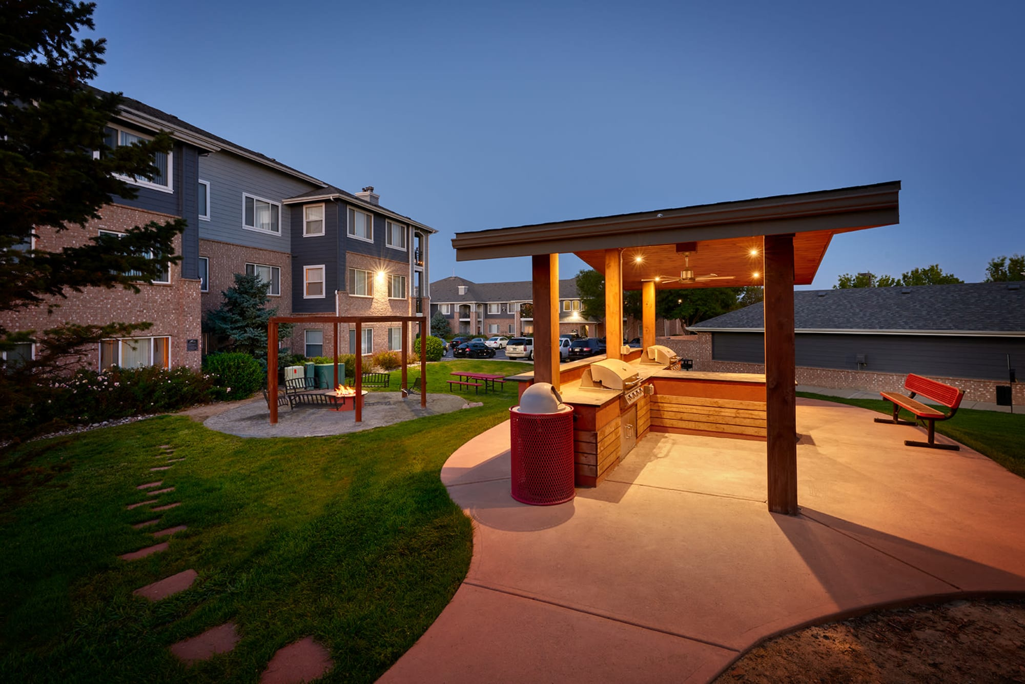 The outdoor picnic area with a firepit, swings, and BBQs at Hawthorne Hill Apartments in Thornton, Colorado