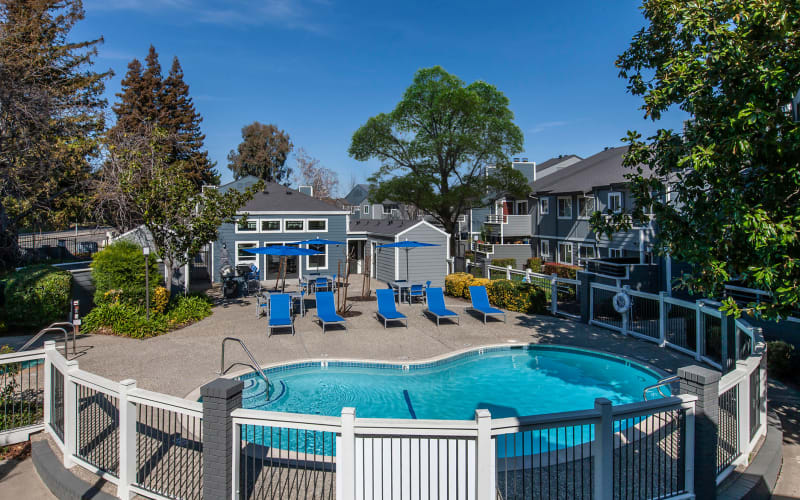 Blue lounge chairs by the pool at Bennington Apartments in Fairfield, California