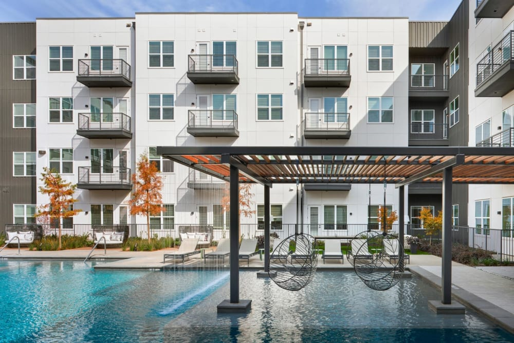 Pergola with hanging wicker chairs over a portion of the swimming pool at 4600 Ross in Dallas, Texas