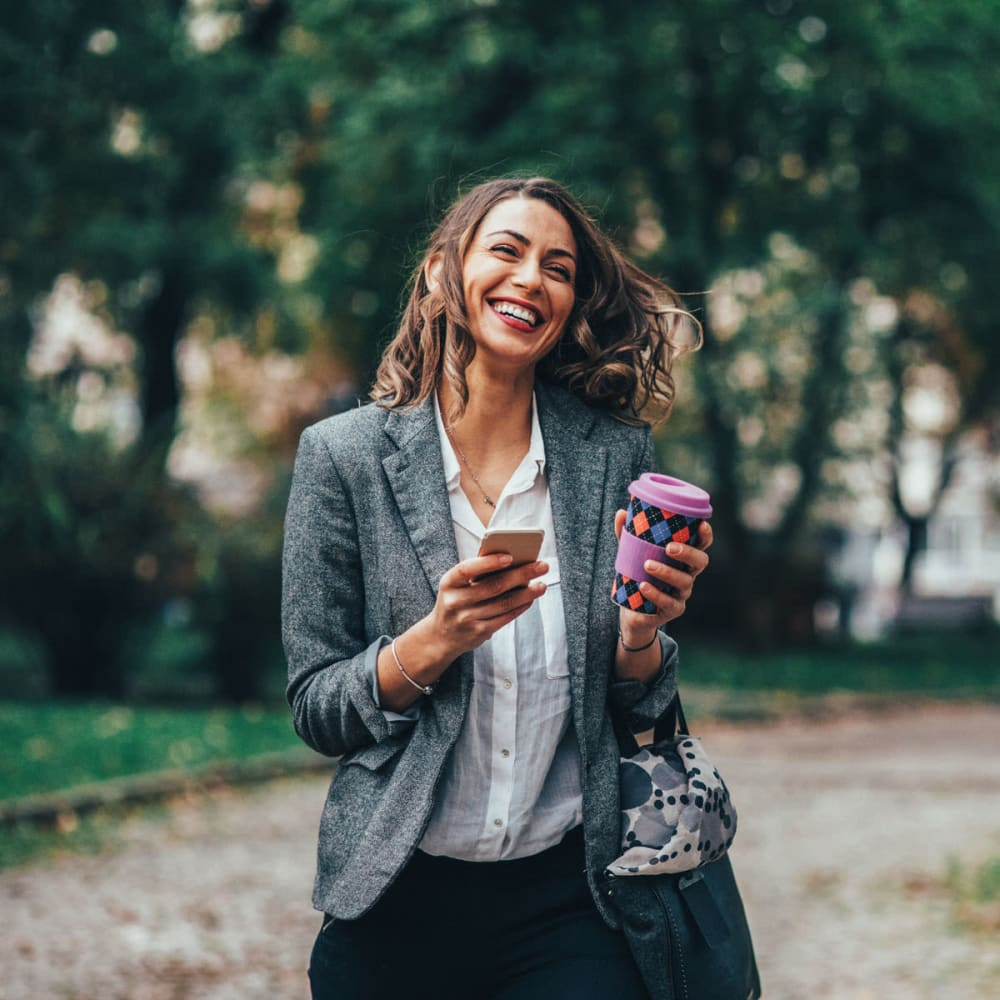 Resident laughing at something on her smartphone while walking to work with her morning coffee near Oaks Station Place in Minneapolis, Minnesota