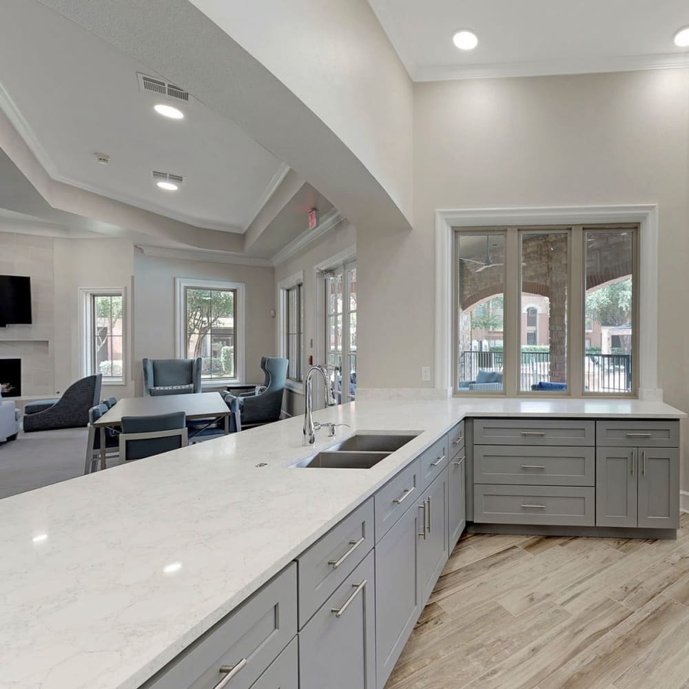 View of the clubhouse lounge over the demonstration kitchen's bar at Oaks Riverchase in Coppell, Texas