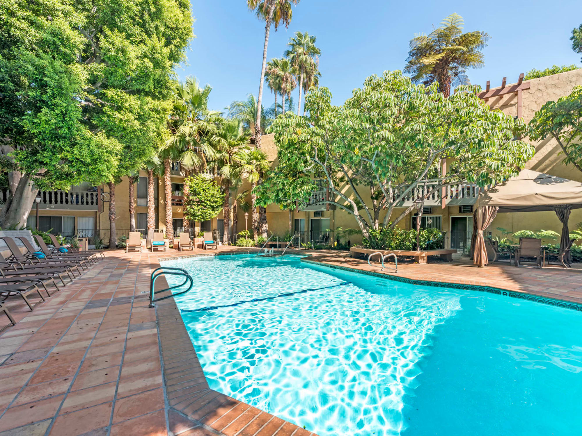 Resort-style swimming pool surrounded by palm trees at Mediterranean Village in West Hollywood, California