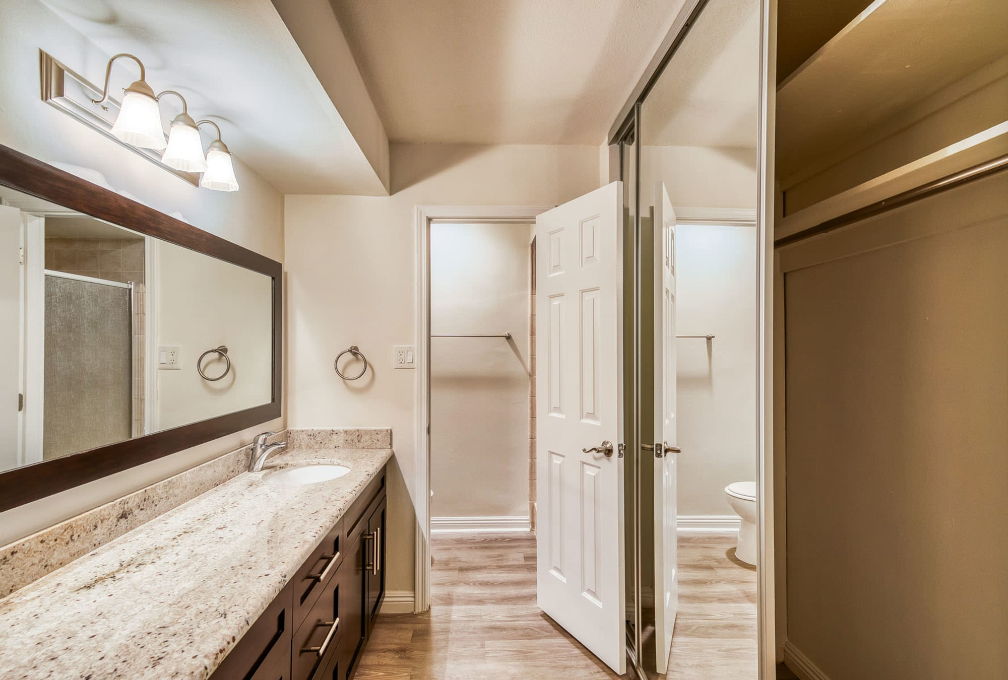 Spacious granite countertop and a closet for storage in a model home's primary bathroom at Mediterranean Village in West Hollywood, California
