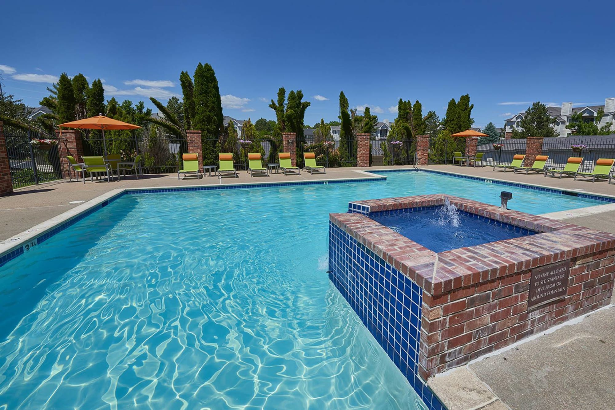 Sparkling pool with a fountain and lounge area at Villas at Homestead Apartments in Englewood, Colorado