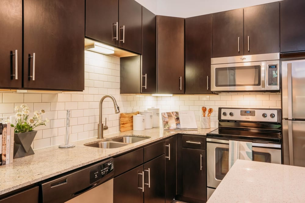 Subway tile backsplash and espresso wood cabinetry in a model apartment's kitchen at Lakeshore Pearl in Austin, Texas