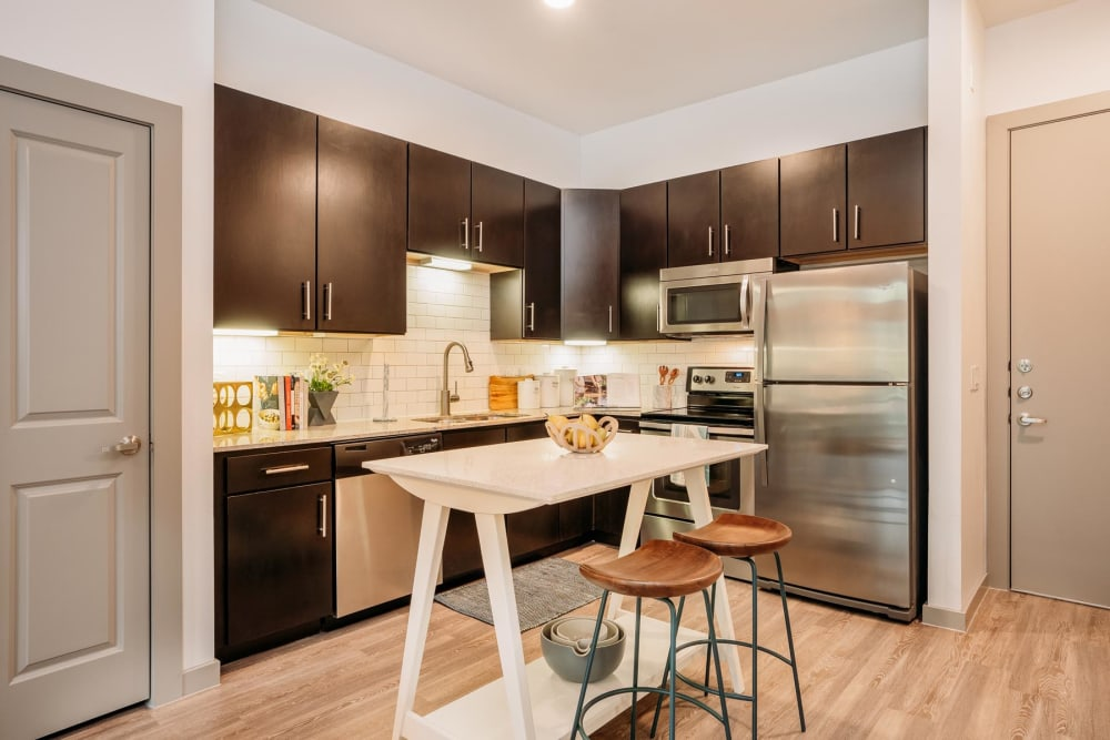 Gourmet kitchen with stainless-steel appliances and quartz countertops in a model home at Lakeshore Pearl in Austin, Texas