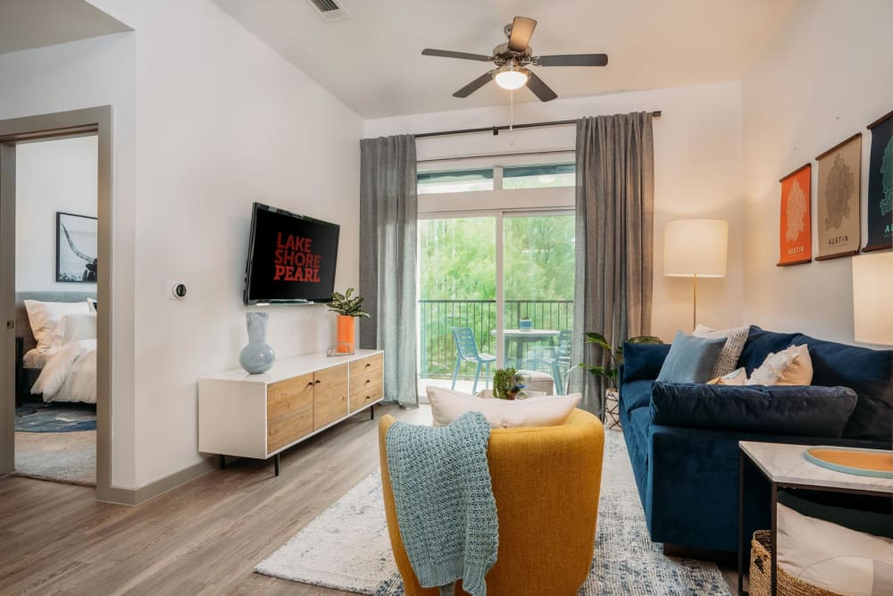 Hardwood flooring and a ceiling fan in the living area of a model home at Lakeshore Pearl in Austin, Texas