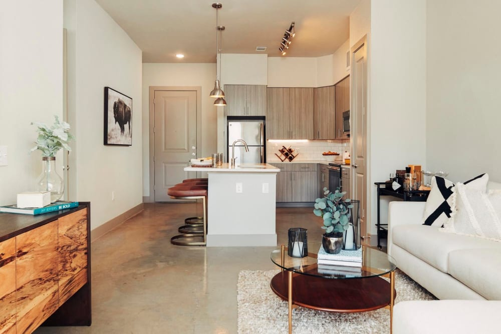 View of the kitchen from an open-concept model home's living area at The Guthrie in Austin, Texas