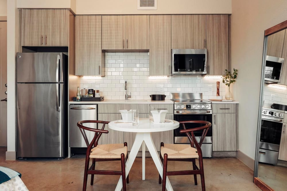 Model apartment's kitchen with a subway tile backsplash at The Guthrie in Austin, Texas