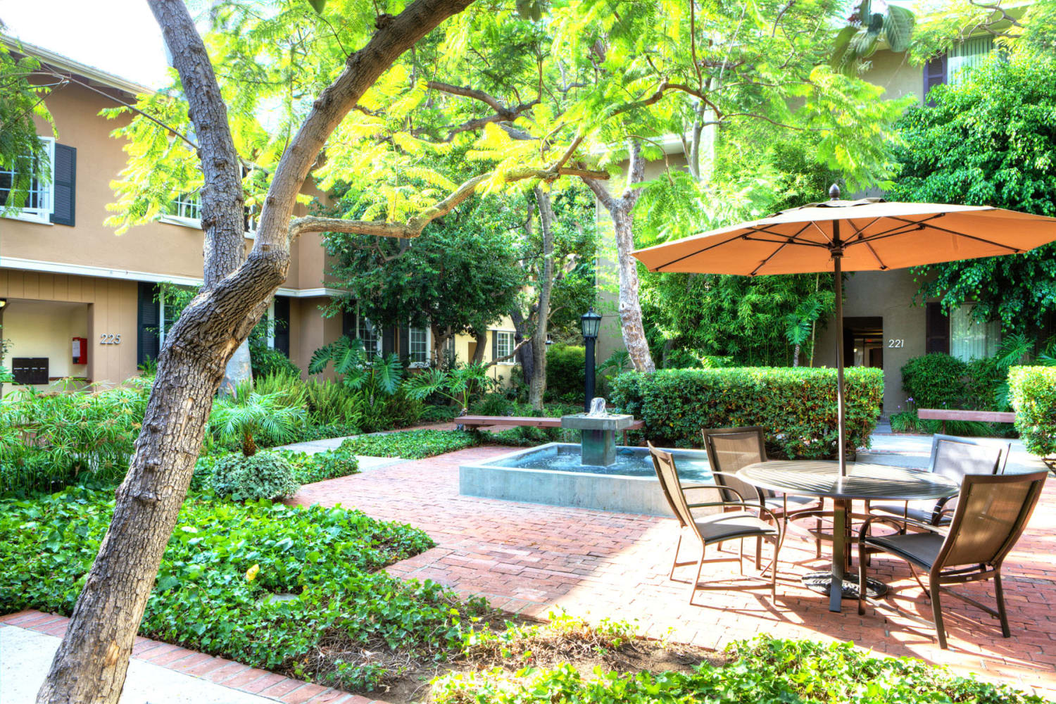 Shaded seating and lush landscaping at one of the courtyards at Sunset Barrington Gardens in Los Angeles, California