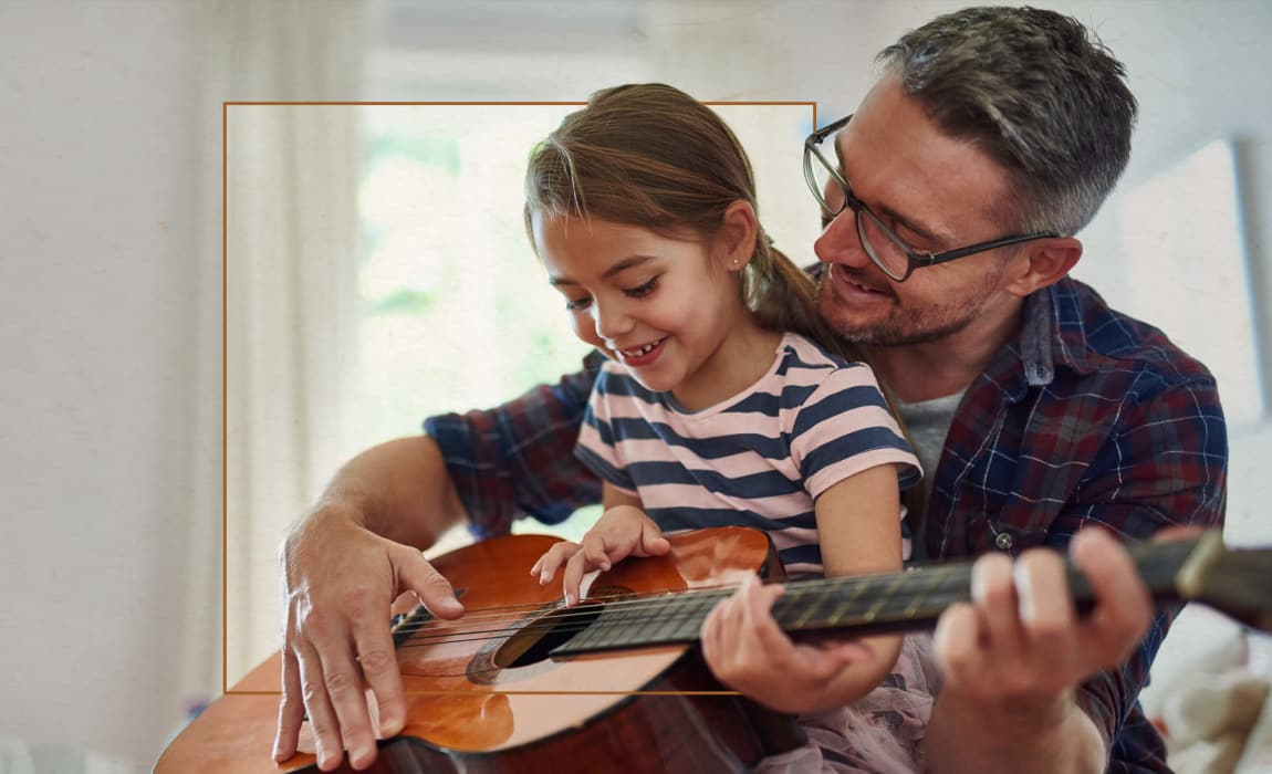 Resident playing guitar with his daughter at Alta Frisco Square