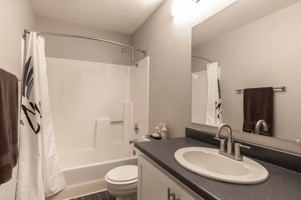 A renovated bathroom with a tub at Avery Park Apartments in Fairfield, California