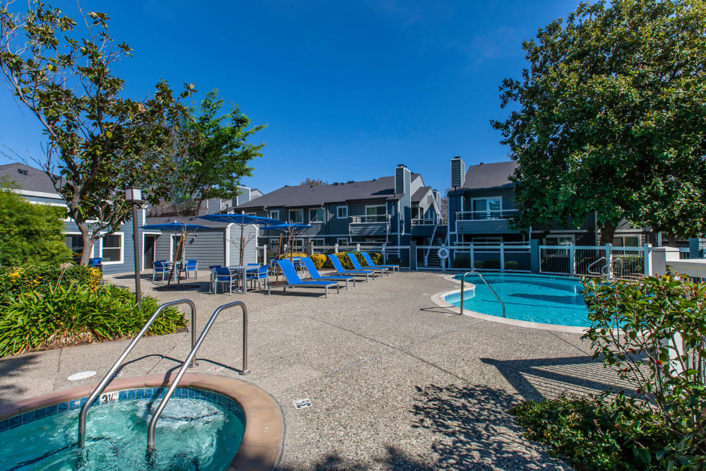 Beautiful resort-style swimming pool and hot tub with a lush backdrop at Bennington Apartments in Fairfield, California