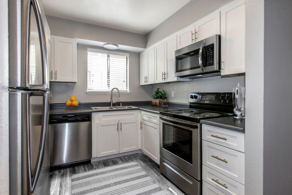 Modern kitchen with white cabinets and stainless steel appliances at Bennington Apartments in Fairfield, California