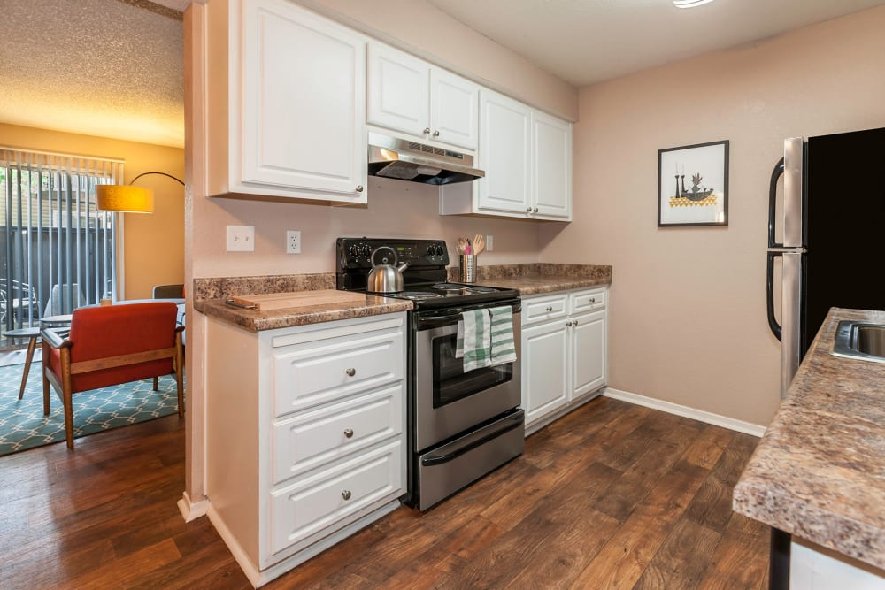 A kitchen with plenty of cabinet space at The Woodlands Apartments in Sacramento, California