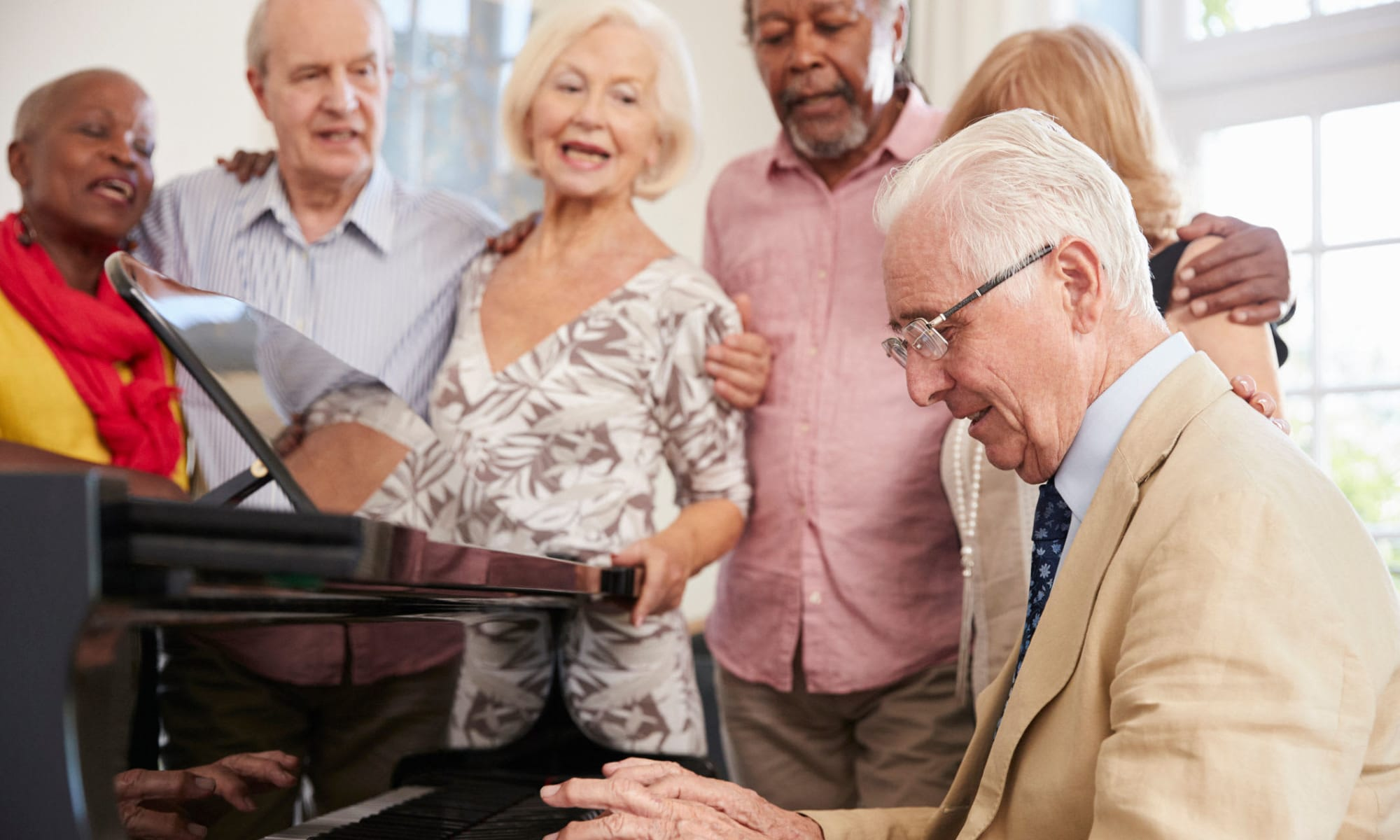 Residents playing the piano and singing at Avenir Memory Care at Scottsdale in Scottsdale, Arizona.