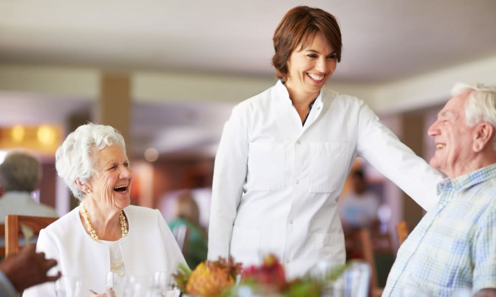 Two residents in the dining hall laughing with a caretaker at Magnolia Court in Vacaville, California