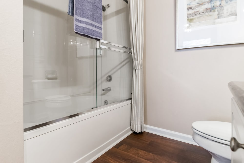 Shower/tub combo bathroom with wood flooring at Marquis at Carmel Commons in Charlotte, North Carolina