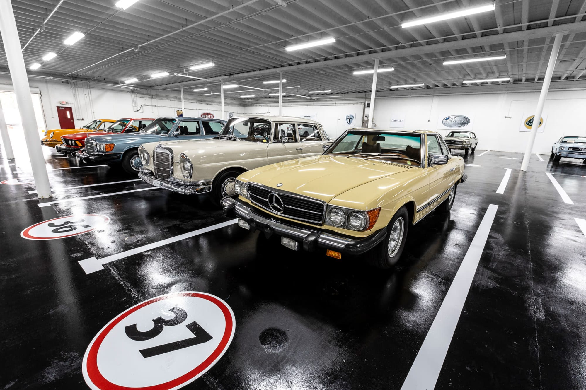 A Mercedes in front of a row of luxury cars inside the secure garage of Premier Car Storage in Miami, Florida