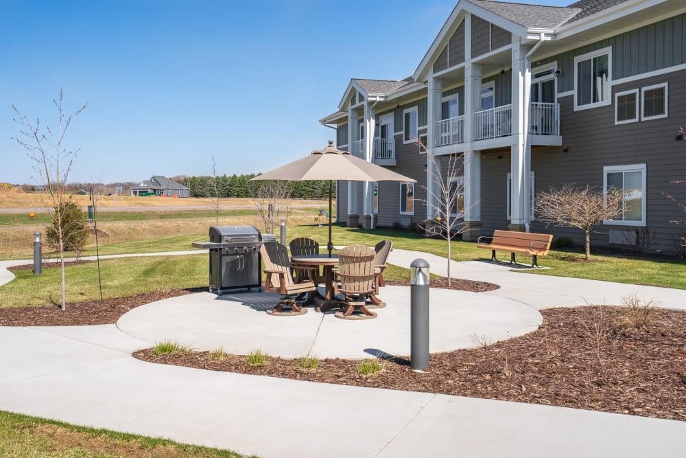 Exterior of building with patio and grill at Arbor Glen Senior Living in Lake Elmo, Minnesota