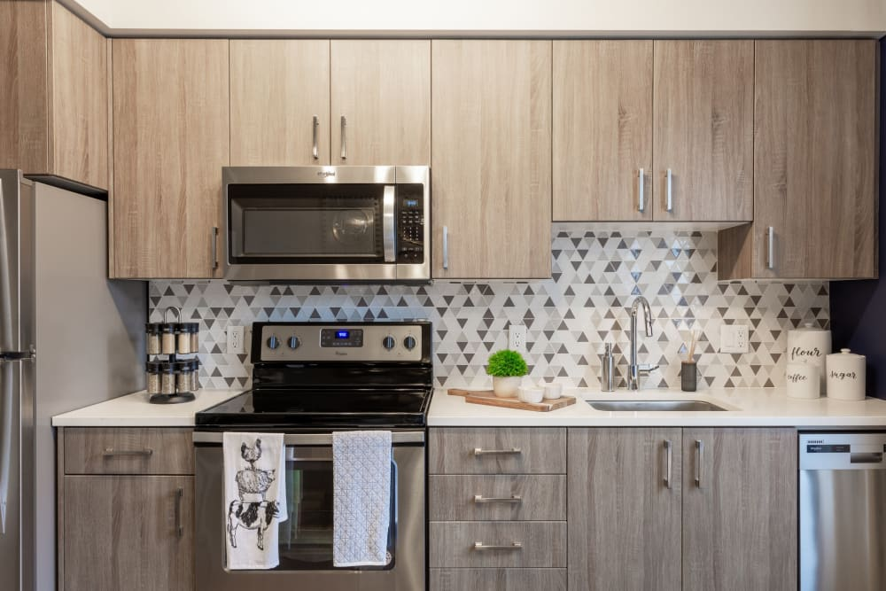 Beautiful custom wood cabinetry and stainless-steel appliances in a model home's kitchen at ArLo Apartments in Portland, Oregon