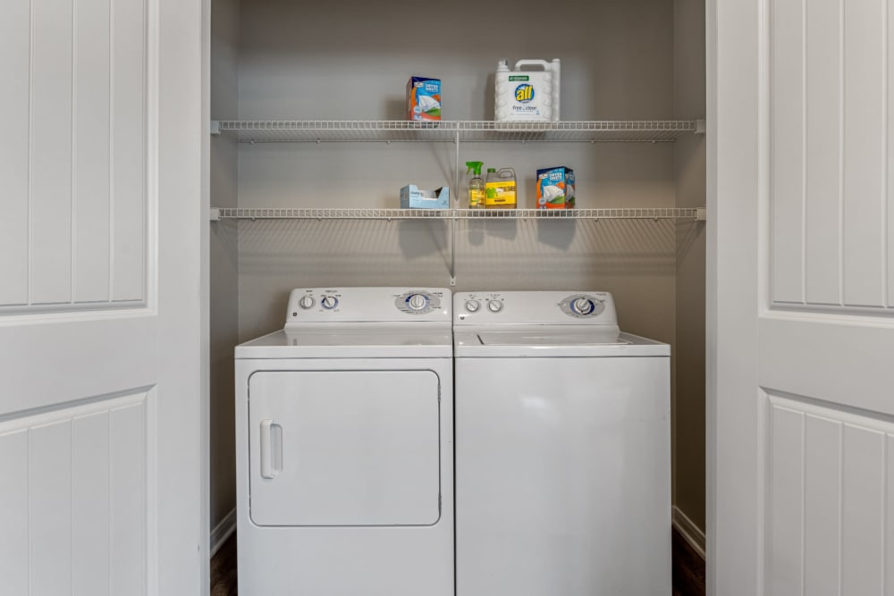 Laundry closet with full size washer and dryer and shelves at Marquis at Sugar Land in Sugar Land, Texas