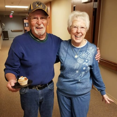 resident couple arm-in-arm walking the hallways at The Oxford Grand Assisted Living & Memory Care in Wichita, Kansas