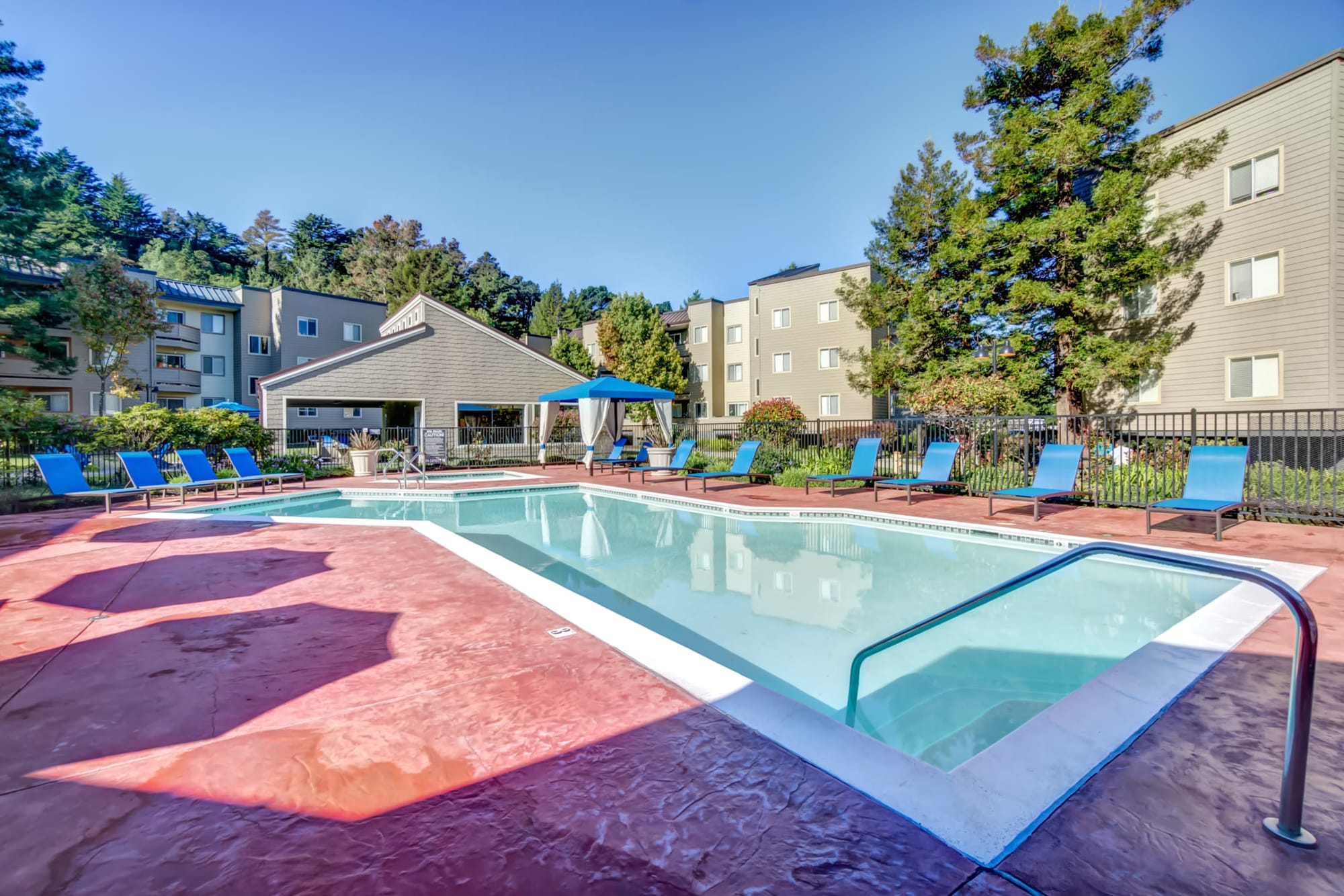 Pool with lounge chairs and view of fitness center at Serramonte Ridge Apartment Homes