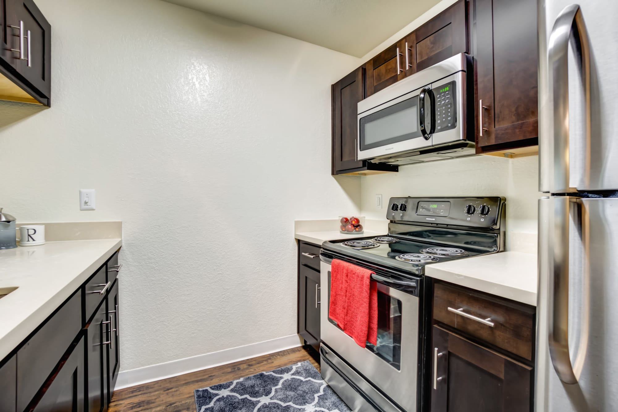 Brown Renovated Kitchen with Stainless Steel Appliances at Serramonte Ridge Apartment Homes