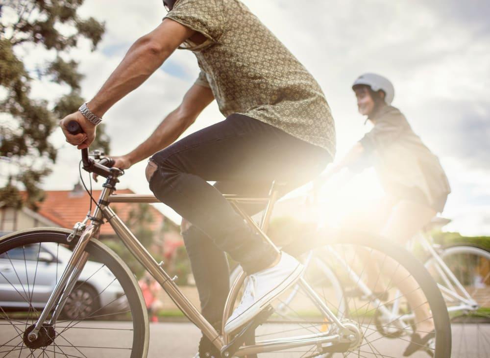 A couple riding bikes in Marina del Rey, California, on their way home to Harborside Marina Bay Apartments