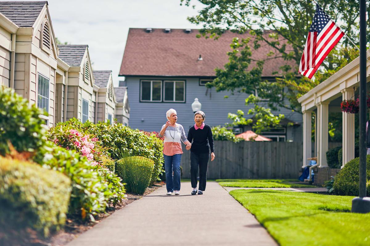 Two residents walking outside at Farmington Square Tualatin in Tualatin, Oregon